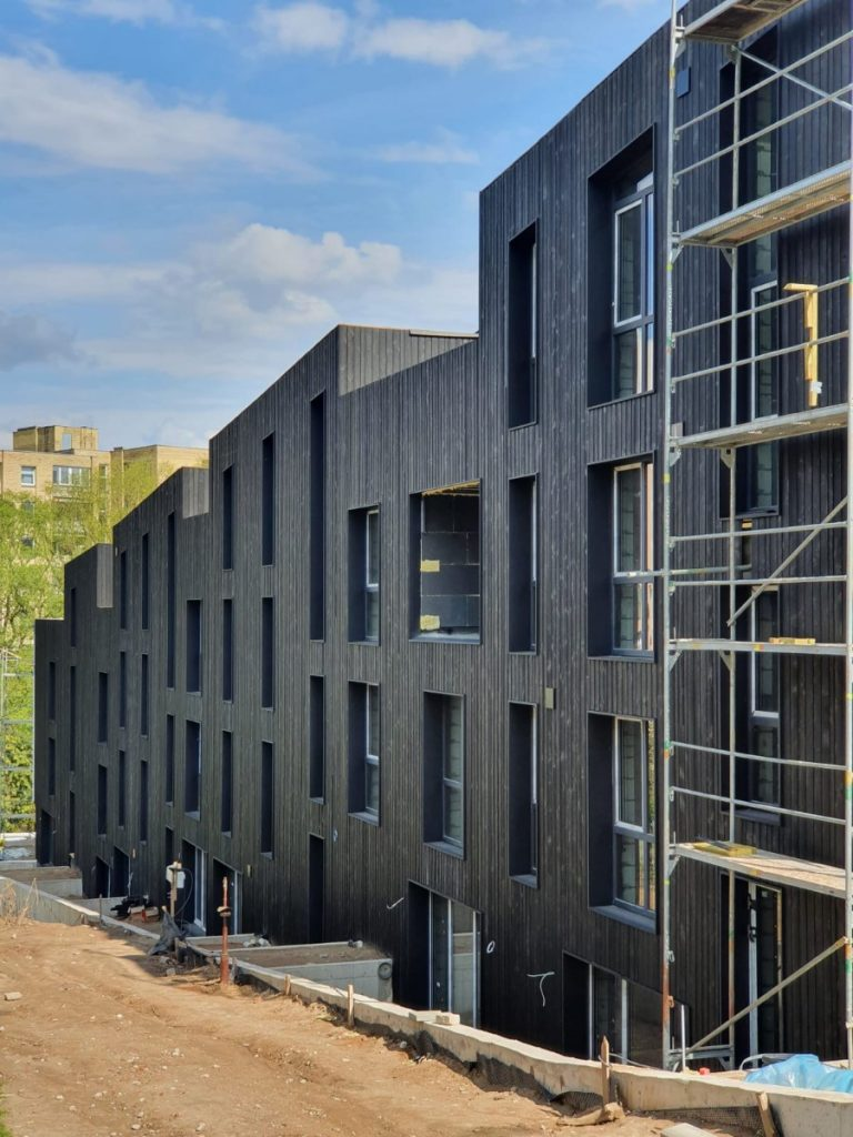 Huge apartment building with charred Accoya wood siding